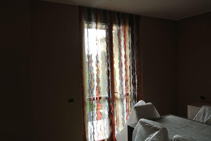 Tende a strisce verticali in organza con combinazioni di colori a scelta, installate a vetro con bacchetta o a soffitto tramite binario velctrato, realizzate su misura.