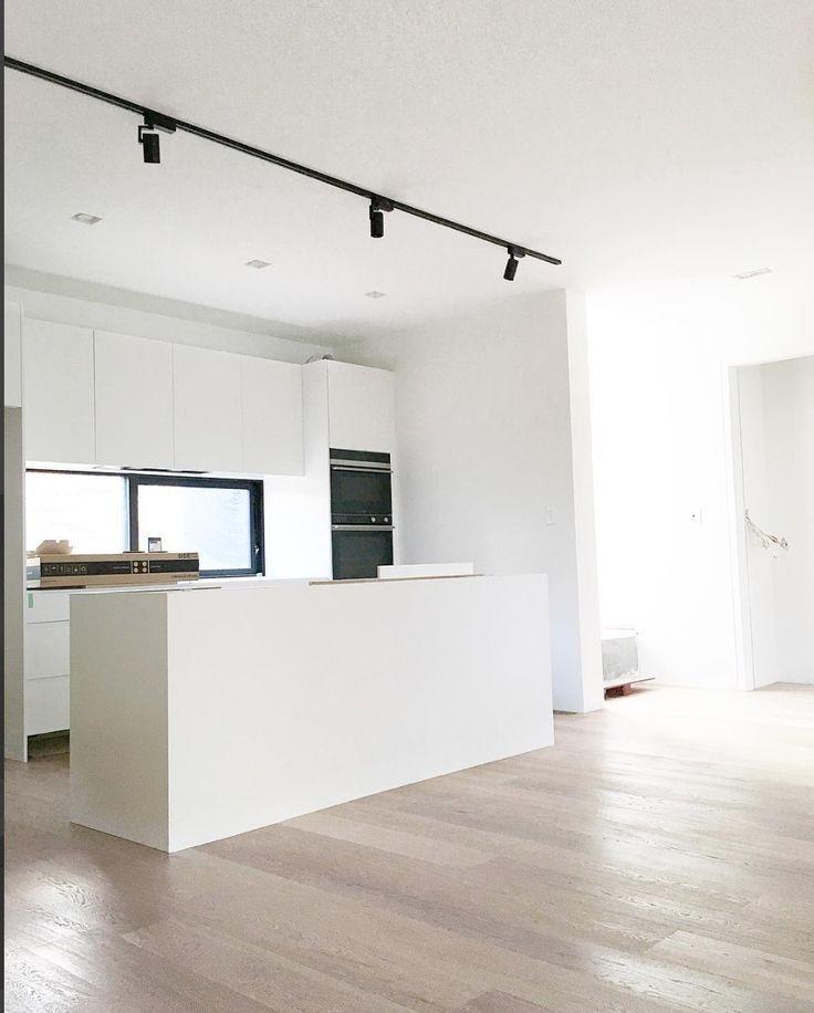 white kitchen with black track lighting