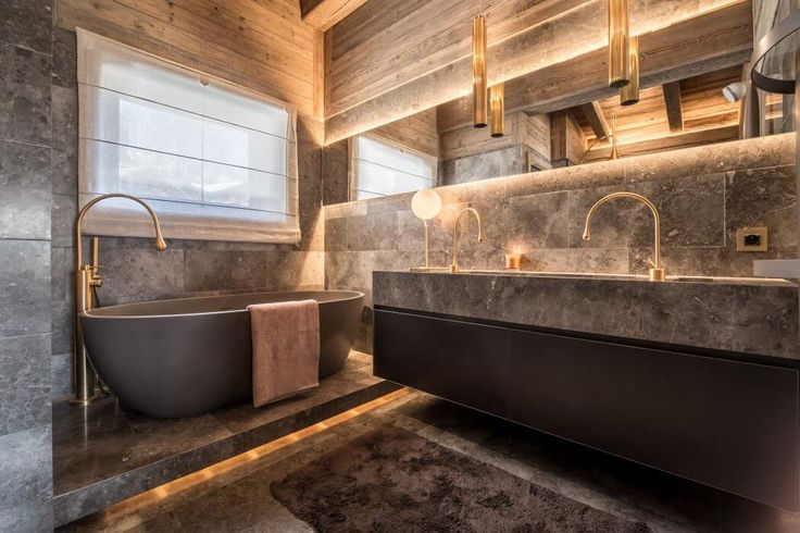 This luxury chaletis situated in Megève, France, was designed in 2017 by Refuge – Architecture D'intérieur.  The bathroom is dressed in gray marble and taps in the shape of golden matte drops.