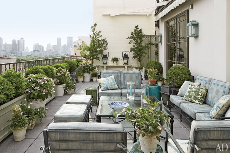 The terrace, where Costos and Smith often host cocktails, features outdoor seating by Kenneth Lynch & Sons, with cushions of a Rose Tarlow Melrose House fabric; the planters at left are by Inner Gardens, the side tables and cocktail table are by Treillage, the standing lanterns are all by Restoration Hardware, and the wall-mounted lanterns are by Charles Edwards.