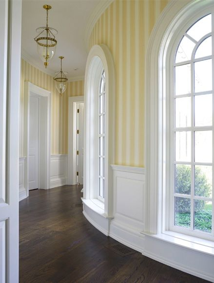 Rounded hallway with butter yellow striped wallpaper, lovely crisp white millwork, and brass lanterns in an addition on a Georgian home in Greenwich, Connecticut by Bunny Williams.