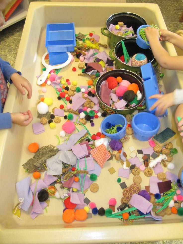 De zandtafel vullen met knoopjes, stof, kurken, bolletjes, en dan sorteren in bakjes; harde en zachte dingen bij elkaar. Ruw en glad.
