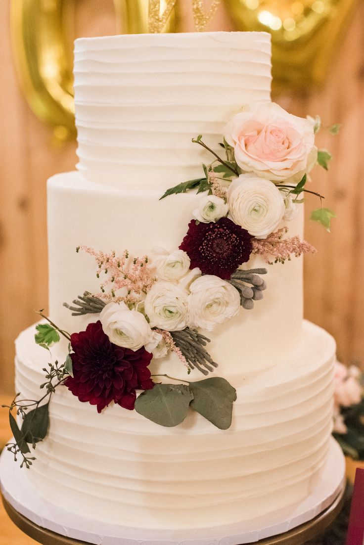 a simple + pretty boho wedding cake --- love the floral swag across all layers <3 the perfect wedding cake for a blush pink + maroon wedding! taken at THE SPRINGS in McKinney, Stone Hall. follow this pin to our website for more information, or to book your free tour! photographer:  Ashley Rains Photography #weddingcake #weddingcakeideas #maroonwedding #pinkwedding #blushpinkwedding #naturalwedding #winterweddingcake #bohoweddingcake