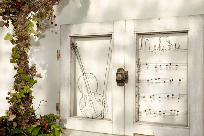 古い扉の枠を額縁に見立てて、バイオリンと楽譜が踊る素敵な作品。