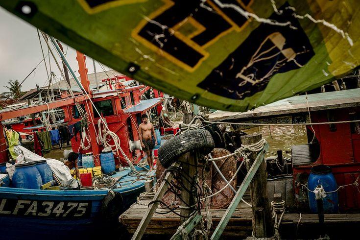 Ian Teh - A Burmese Migrant Fisherman Oversees the Boat as it Docks. Sekinchan.  ianteh.com