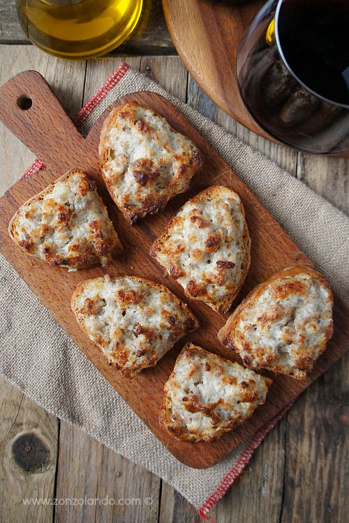 Crostini con salsiccia e stracchino ricetta tipica toscana antipasto - starter sausage and cheese crostini bread typical tuscan recipe