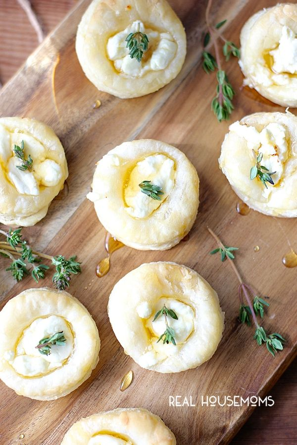 Overhead shot of Goat Cheese and Honey Bites on a cutting board with thyme and honey drizzle