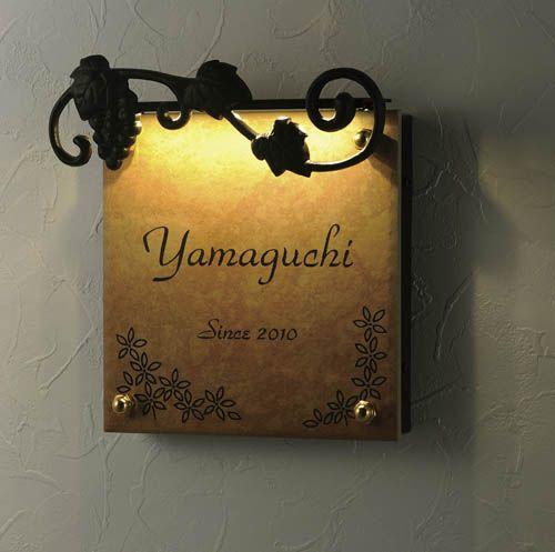 夕暮れの玄関に柔らかに浮かび上がるロートアイアンと磁器質タイル表札