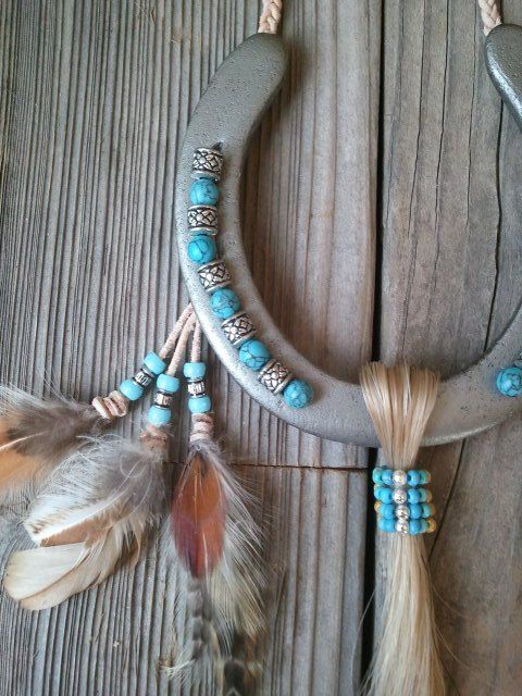 """A clean, clear horseshoe decorated with turquoise and silver beads in the grooves, a leather lacing braided hanger, choice of color of horse hair, and feathers.  This horseshoe measures approximately 4 ½"""" x 5"""" (just a bit larger than the average size of an adult's palm). The design uses a clear painted horse shoe and is painted to protect it from rusting again. Because it is a clear color, you can still see all the dents and scratches on the horse shoe from the horse that wore it. I wrap the…"""