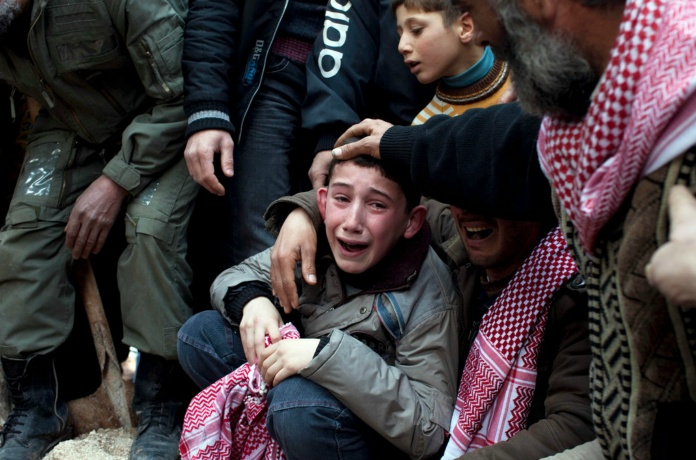 Death of a father. Abdulaziz Abu Ahmed Khrer was killed by a Syrian Army sniper. His son, Ahmed, was among the mourners at his funeral in Idlib, in Syria's north.    Photography by; Rodrigo Abd.