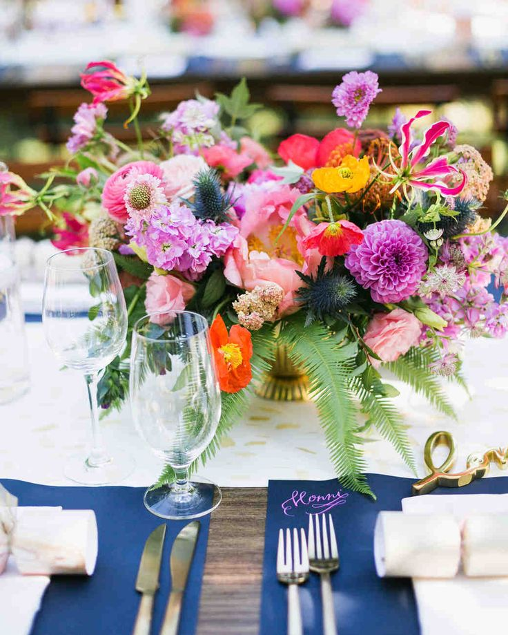 A Fun, Colorful Wedding in Guerneville, California | Martha Stewart Weddings - Colorful floral arrangements by Scarlett & Grace featured dahlias, poppies and ranunculus, and were set in lush gold vases served as centerpieces. #weddingflowers #weddingideas #centerpieces #wedding
