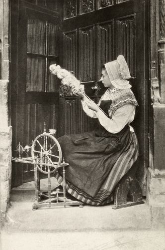 A young woman, in a traditional costume, spins wool inside a house.  Location:Normandy, France.