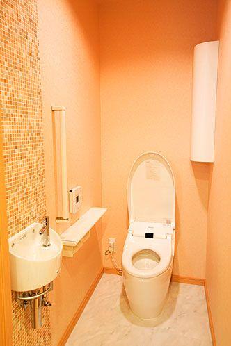 壁面に天然石のタイル使用して、オレンジ色でまとめました。