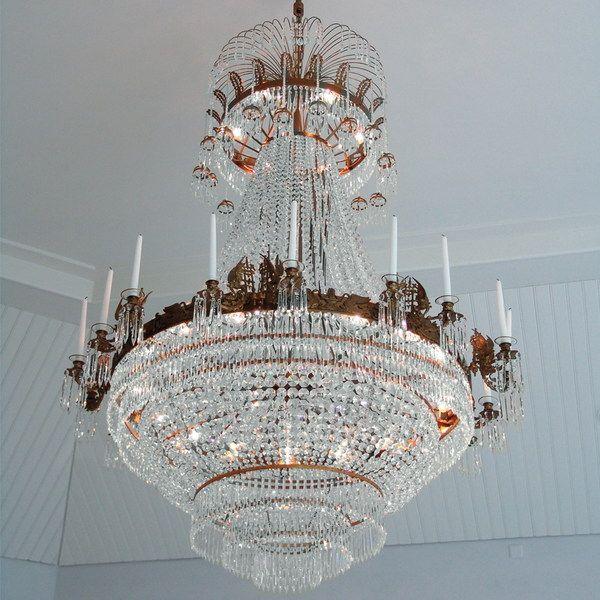 LYSEKRONE HERAKLES MAGNIFIK Lysekroners ramme er av oxide finish og har ornamenter og dekorasjoner med griffon symboler. Det har 12 holdere for stearinlys, fordi armene for stearinlys lys er plassert to og to.Lysekrone med levende lys.
