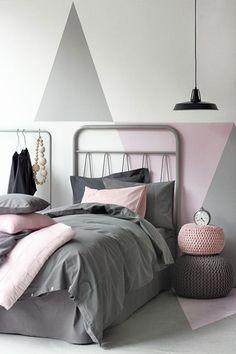 Sur le mur d'une chambre ado fille un jeu de grands triangles dessinés en rose tendre et gris perle sur un fond blanc. En harmonie lit linge et poufs de sol dans les mêmes tons.