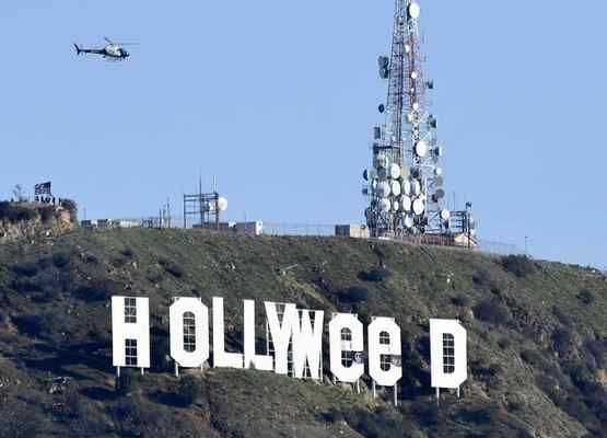 """An LAPD airship flies by the Hollywood sign Sunday after New Year's Eve pranksters changed the sign to read """"Hollyweed."""""""