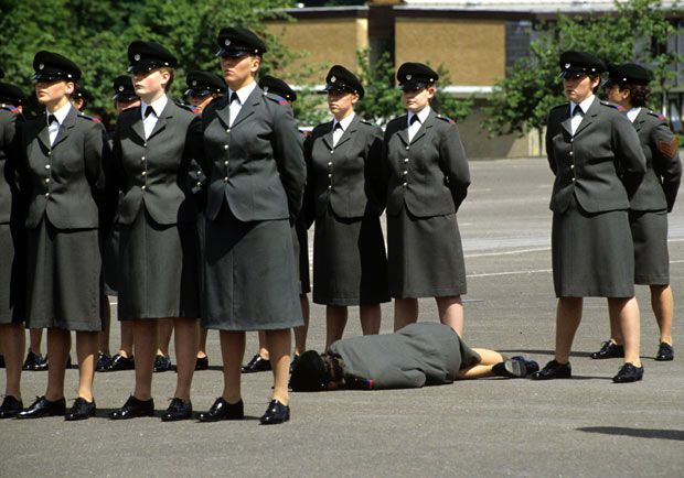 A member of the Women's Royal Army Corps lies on the parade ground after fainting during the Queen Mother's visit to the WRAC Centre in Guildford, Surrey