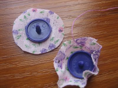 use I have only odd colours left over from my nappy making days)  Needle, thread, scissors, scraps of fabric and a glue stick, (very essential sewing accessory)  Step 1: Using the glue stick, glue you snap cap onto the scrap of fabri