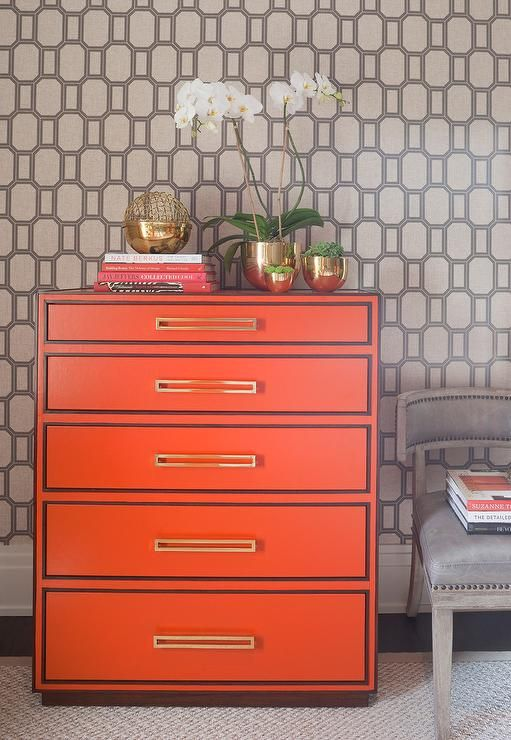 Orange and gray bedroom features a wall clad in Phillip Jeffries What a Gem Silver on White Manila Hemp Wallpaper lined with a Hermes orange chest of drawers, Lexington Home Aquarius Aria Chest, topped with Arteriors Stockholm Containers next to a gray nailhead chair by Mecox Gardens.