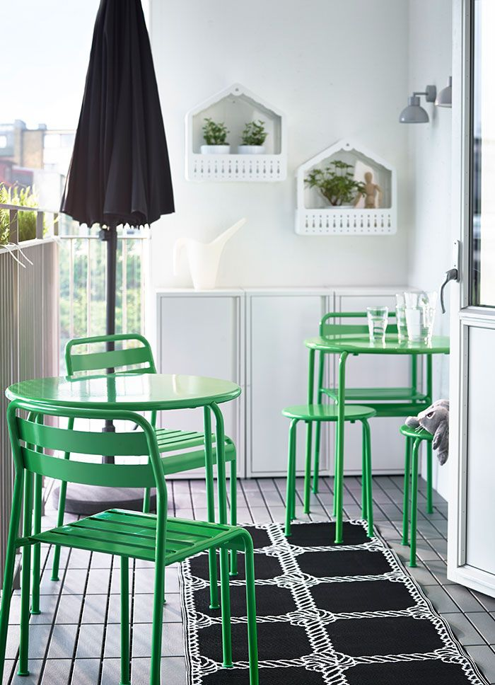 A balcony with two green round tables, stools and chairs, a black parasol and three white steel cabinets