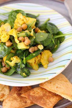 Een heerlijke en voedzame salade van spinazie, geroosterde bloemkool, kikkererwten, avocado en knoflook pitachips uit de oven. Bekijk hier het recept.