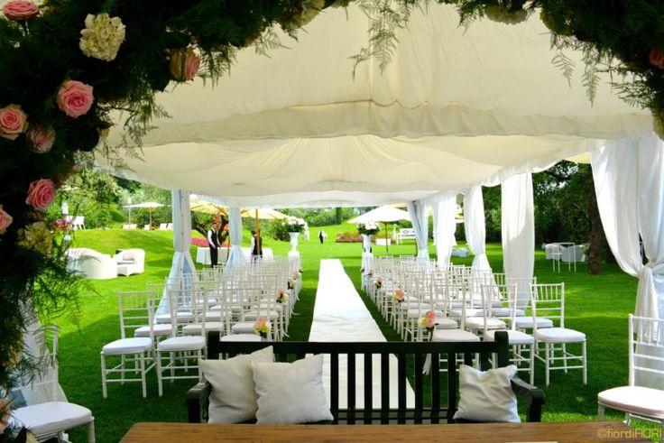 Zona cerimonia con arco e sedie decorati con ortensie e rose dai toni delicati