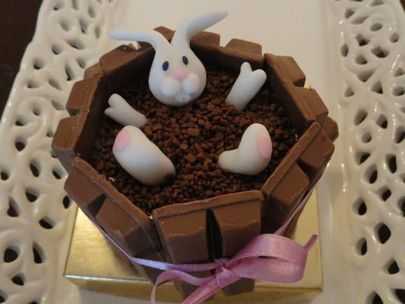 Cupcake de chocolate, coberto com brigadeiro, tina de chocolate Kit Kat e coelho em pasta americana. Acompanha embalagem em caixa unitária com base cartonada e tampa em acetato transparente amarrado com laço de fita. R$ 35,00