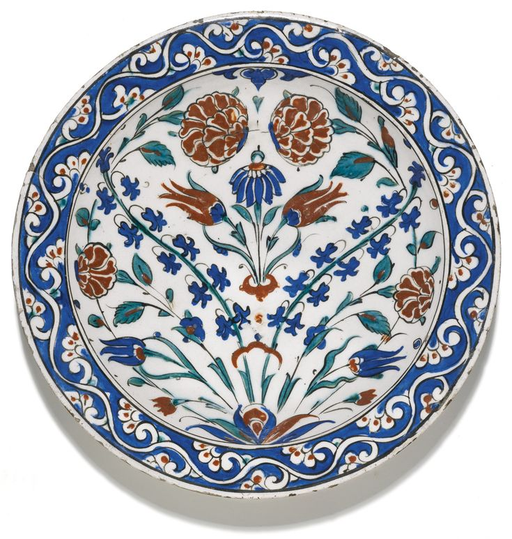 A large Iznik polychrome pottery dish, Turkey, circa 1580 -    of shallow rounded form, decorated in underglaze cobalt blue, viridian green and relief red with black outlines, featuring a leafy tuft emanating sprays of tulips, carnations and hyacinths, the rim with a foliate vine on a blue ground, reverse with floral motifs and old collection label 33.5cm. diam.