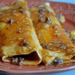 Simple and quick beef enchiladas. Ground beef and onion are wrapped in flour tortillas, topped with Cheddar cheese and black olives, then baked. This is also great with leftover chicken, shredded beef or turkey. Serve with a green salad or beans and rice.