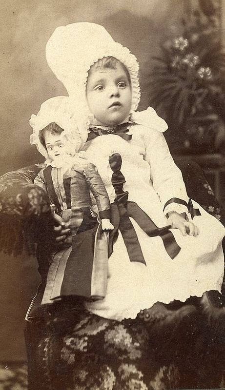 Antique photo of little girl and her doll, circa 1880 - 1900.