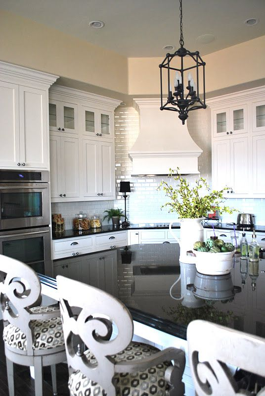 White cabinetry + black counters + white subway tile + black light fixture + stainless steel appliances