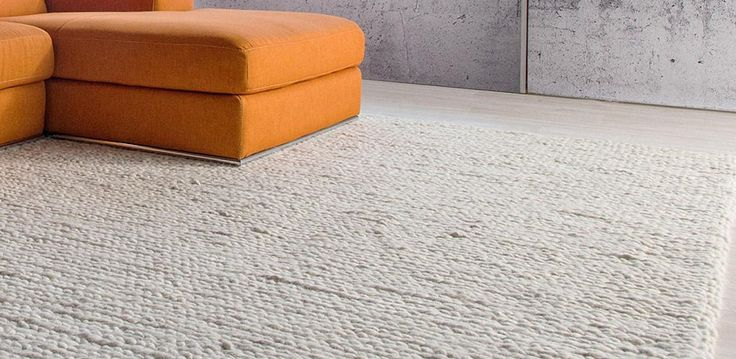 A hand-woven rug with a weaved pattern, made from 100% wool. Available in 2 sizes in Ivory or Grey.