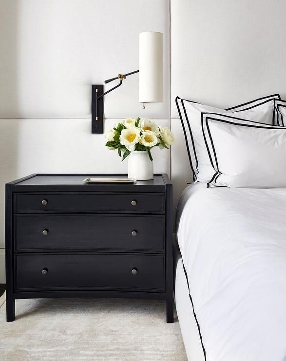 Chic white and black bedroom boasts a tall white padded headboard covering the wall behind a bed dressed in white hotel bedding topped with black border shams lit by a headboard mounted modern swing arm sconce fixed over a curved black 3-drawer nightstand placed on a light gray rug.