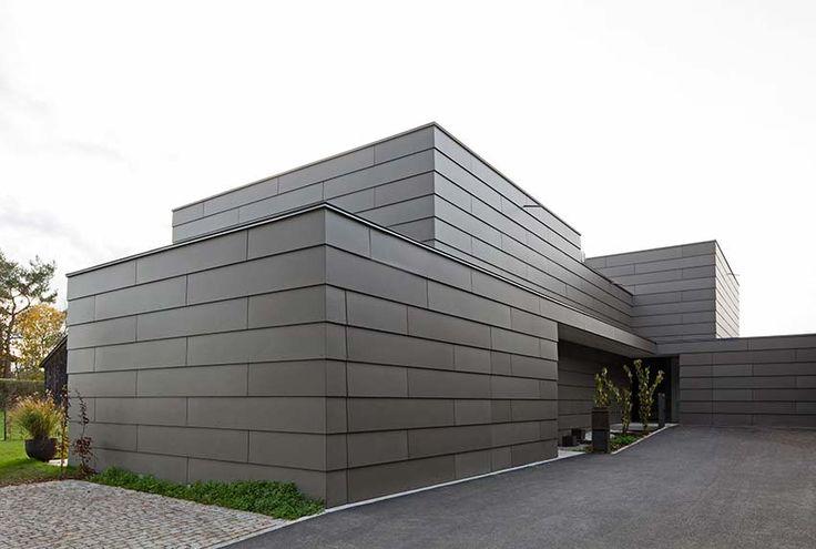 Horizontale Fassadenbänder verbinden die beiden modernen Doppelhaushälften zu einer Einheit. In Stülpschalung auf Holz-UK verlegt bilden die durchgefärbten und braun lasierten Equitone Natura Fassadentafeln von Eternit eine werthaltige Gebäudehülle, in der