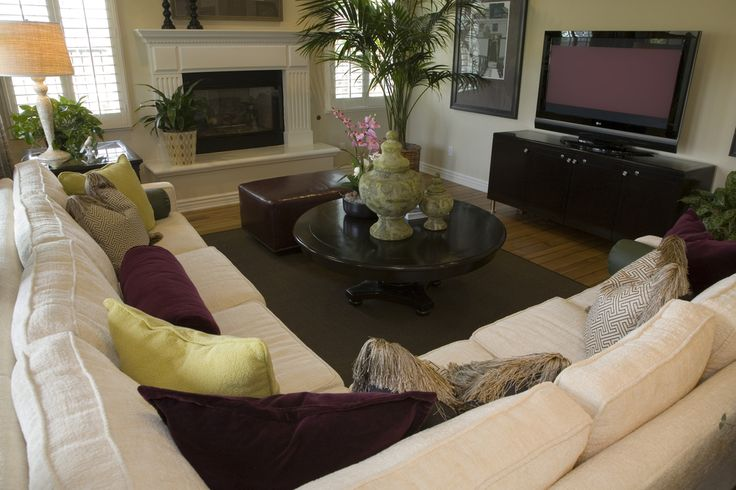 Family room and living room combo with large L-shaped sofa facing a fireplace and large screen television.