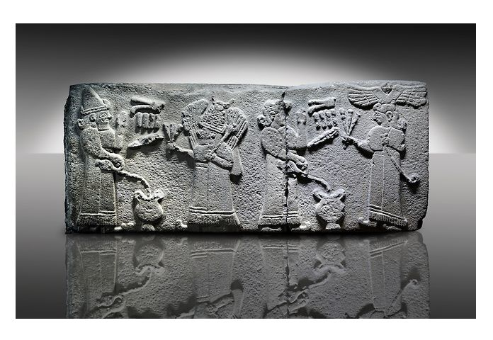 Picture & image of a Neo-Hittite orthostat with a releif sculpture a libation for the gods from Aslantepe , Malatya, Turkey. The figure on the far left is beleived to be a king. He is facing a Bearded God wearing a bore tusk helmet. The God is holding a 3 pronged object and has a club resting on his shoulder. | © Paul E Williams 2013