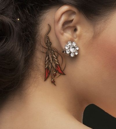 indian feather with ribbon tattoo behind the ear