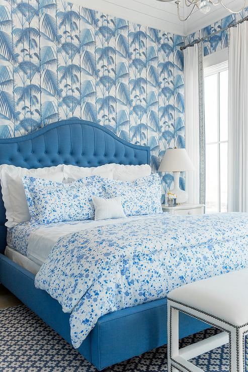 Coastal Living Showhouse - Chic blue bedroom features walls clad in Cole & Son Palm Jungle Wallpaper lined with a blue tufted bed dressed in blue paint splatter bedding, Biscuit Home Austin Bedding, as well as white scalloped shams next to a white nightstand and a white glass lamp atop a blue geometric rug, Dash & Albert Samode Denim/Ivory Indoor/Outdoor Rug.