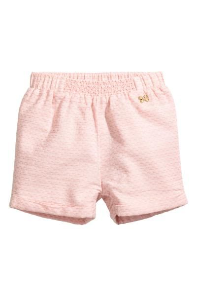 Shorts in a soft cotton weave with an elasticated waist with decorative smocking centre front, a butterfly-shaped decorative metal button at the top and sew