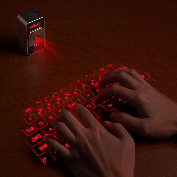 Description: Made for the fat-fingered iPad and iPhone user, The Cube Laser Virtual Keyboard, a 63-key QWERTY holograph. Connects via Bluetooth, key clicking sound effects, 150-hour battery power with rechargeable USB cable. Helping to curb embarrassing epic auto-correct fails; impervious to the debilitating effects of muffin crumbs, spilled coffee, and angry fists.