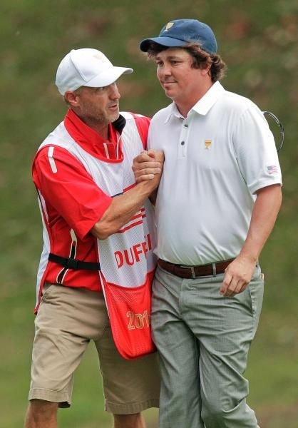 United States team player Jason Dufner, right, greets caddie  Kevin Baile