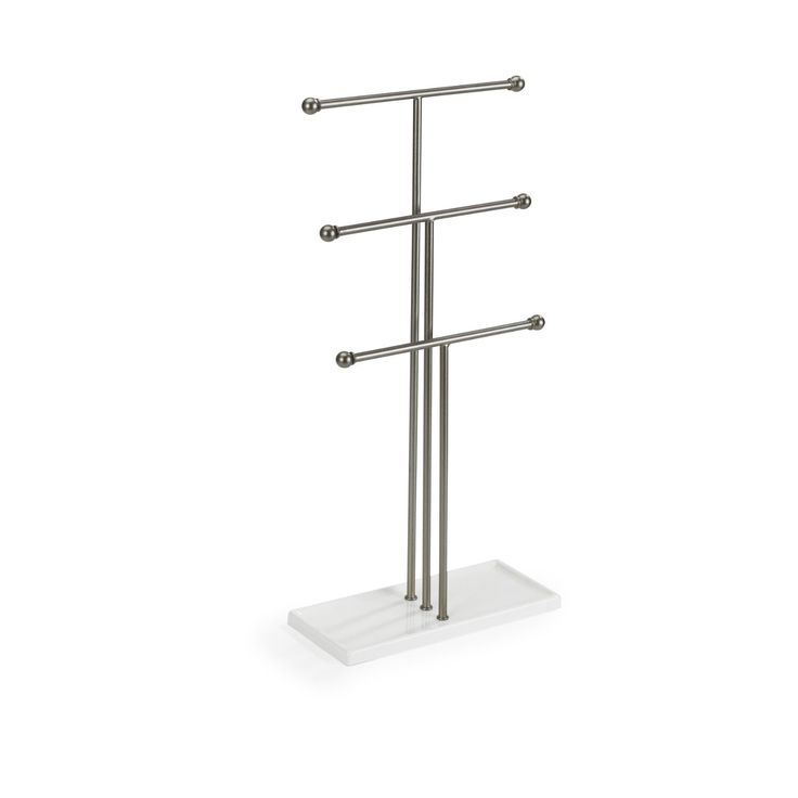 The Trigem jewelry stand organizes and displays necklaces, bracelets, rings and more Three bars arranged in tiers provide ample storage space and the extra-tall design accommodates long necklaces Constructed of steel with a nickel powder-coated finish, the stand rests on a high-gloss white rectangular base that doubles as a tray for rings and other small items Trigem measures 19 by 9 by 4-Inch overall Designed by Alan Wisniewski for Umbra
