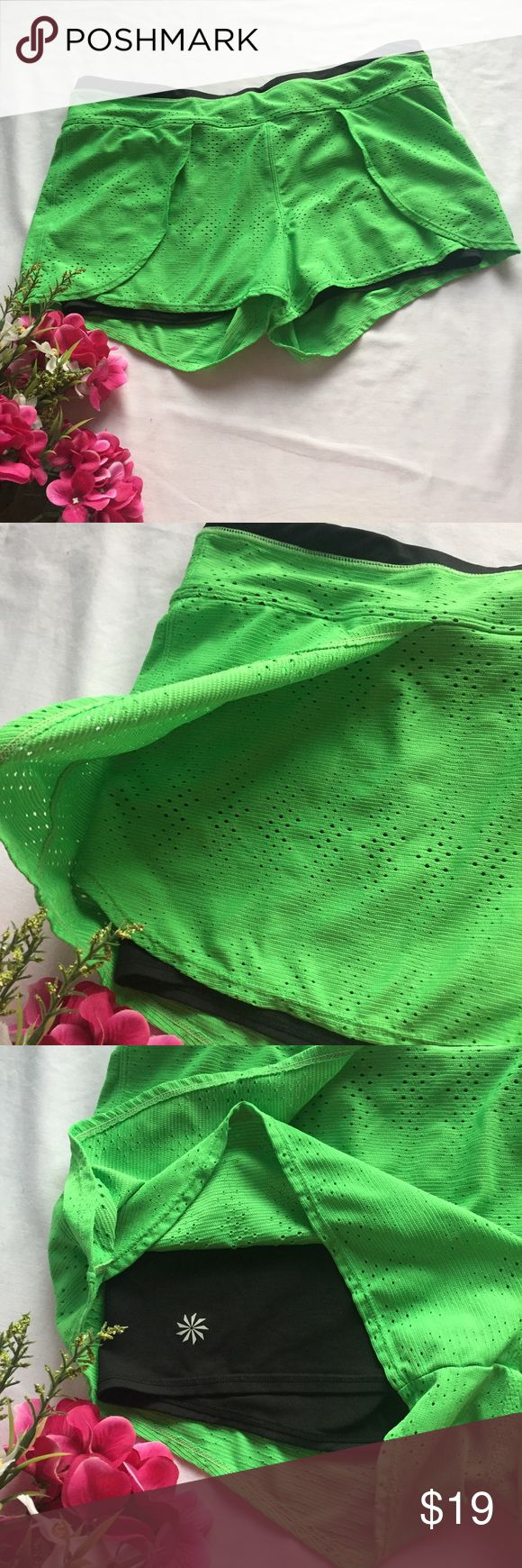 Athleta Lime Green Lined Perforated Sport Shorts Lime green shorts from Athleta. Spandex shorts on the interior with plenty of stretch for a close fit. Lime green looser shell that's Perforated for breathability and has a faux wrap look on each side. Zipper pocket on back, key pocket on interior as well as a draw string. Excellent condition with no flaws. Waist measurement is included in the last picture. (Location I) {no trades - no modeling} Athleta Shorts