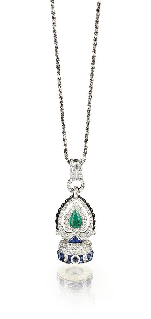 AN ART DECO MULTI-GEM AND ENAMEL WATCH PENDANT, BY CARTIER - With nickel finished lever movement jeweled to the silvered dial enclosed in a champlevé cream enamel bezel with Roman chapters, circular case with pavé-set diamonds and buff top sapphire, surmounted by a pear-shaped emerald within a diamond-set and black enamel Persian motif frame, mounted in platinum, suspended from a gold rope chain of later addition, 1926