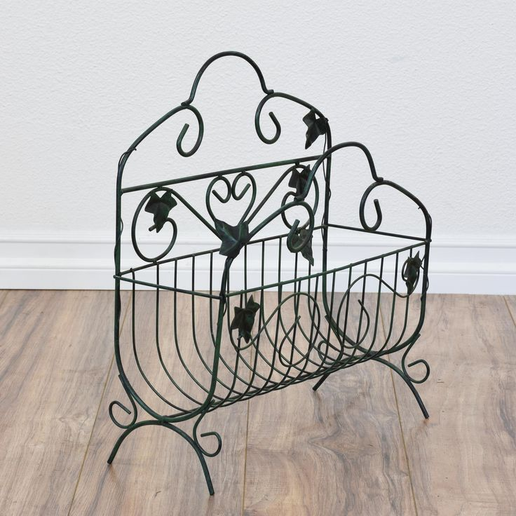 This magazine rack is featured in a durable bent metal with a dark green finish. This end table is in great condition with swirl details, a curved base and ivy leaves. Perfect for storing books and magazines! #mediterranean #storage #magazinerack #sandiegovintage #vintagefurniture