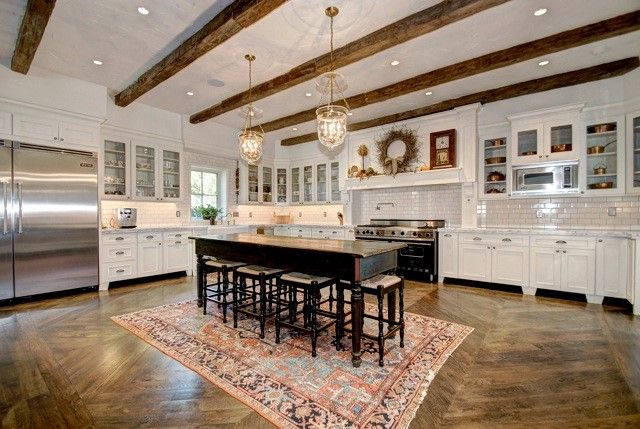 Design 101: What is Cottage Style? – Cottage styling is focused on carefree living, where every element  conspires to create a casual environment for comfort and relaxation. A large scale #CottageKitchen design with a kitchen island table, rustic ceiling beams, white subway tiles, glass cabinet doors, and a grand #white painted wood hood… Read more  on the #DuraSupreme #Blog     #cottage #cottagestyle #interiordesign #cabinetry #cabinets #whitecabinets #whitekitchen