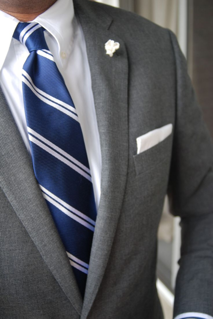 Light grey suit, white shirt with button down collar, blue tie with white stripes