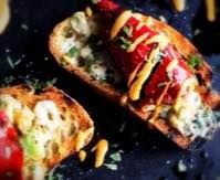 CRAB CHILI DOLMATE CROSTINI  Spicy red chilies stuffed with crab  stewed in a seafood stock of shrimp and crab shells oozing with lemons and Greek spices we finish it with a drizzle of sweet yellow pepper cream sauce