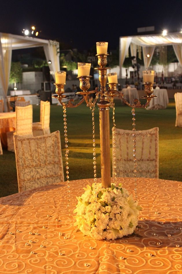 An antique candle stand with flowers, as a table centrepiece. #indian #wedding #decor