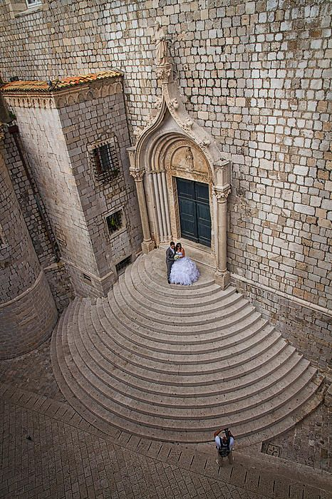 Photograph by Stuart Litoff.  A bride and groom have their wedding portrait taken on the stairs of the Dominican Monastery in Dubrovnik, Croatia.